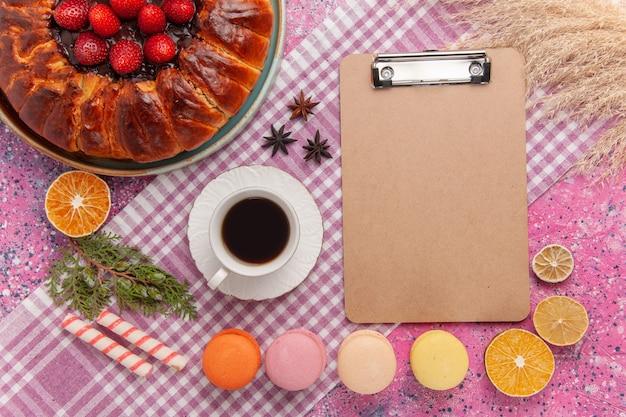 Bovenaanzicht lekkere aardbeientaart met franse macarons op roze