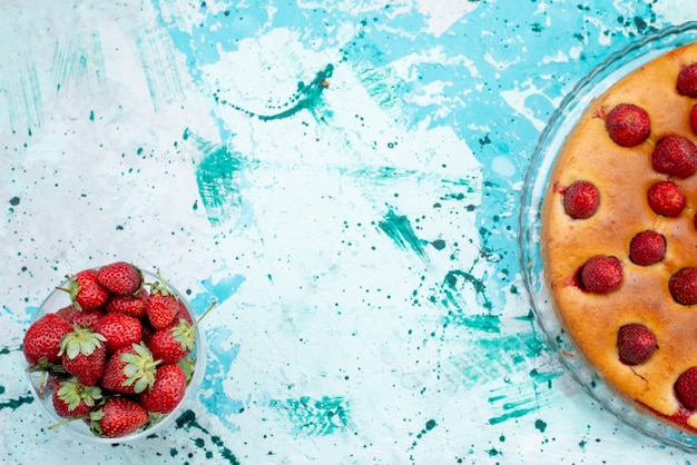 Bovenaanzicht lekkere aardbeientaart met fruit en samen met verse rode aardbeien op het helderblauwe bureau cakedeeg zoete koek fruitbes