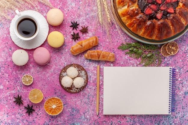Bovenaanzicht lekkere aardbeientaart met kopje thee en macarons op roze