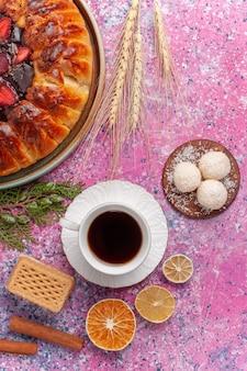 Bovenaanzicht lekkere aardbeientaart met kopje thee op het lichtroze