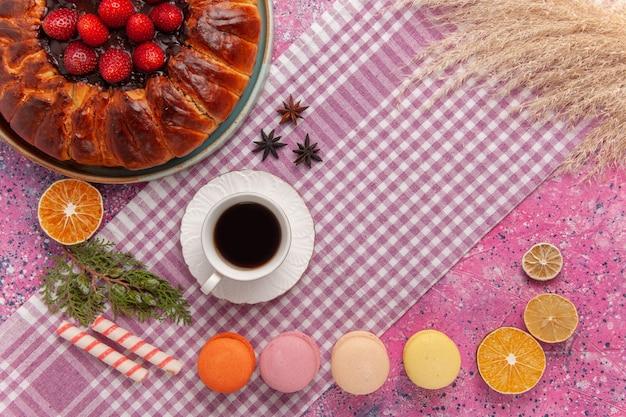 Bovenaanzicht lekkere aardbeientaart met macarons en thee op roze