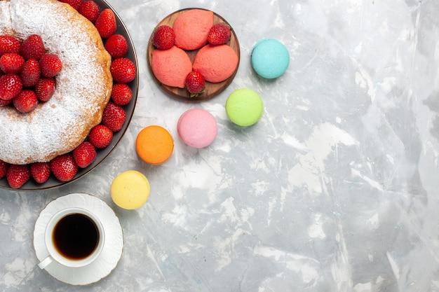 Bovenaanzicht lekkere aardbeientaart met macarons op wit