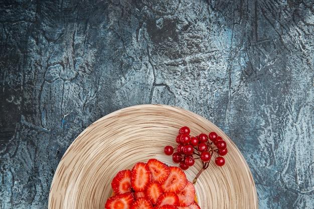 Bovenaanzicht lekkere aardbeientaart met rode bessen op donker bureau