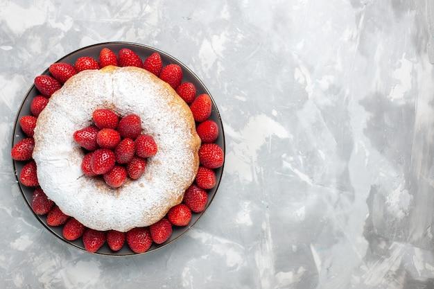 Bovenaanzicht lekkere aardbeientaart met suikerpoeder op wit