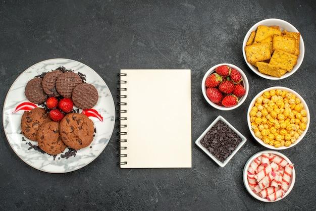 Bovenaanzicht lekkere biscuit plaat met stukjes chocolade verse aardbeien en kommen koekjes lieverd op zwarte achtergrond met vrije ruimte