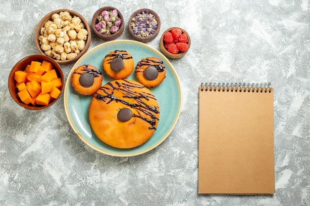 Bovenaanzicht lekkere cacaocakes met chocoladesuikerglazuur en bloemen op witte oppervlaktekoekje, zoete cake, dessertkoekjestaart
