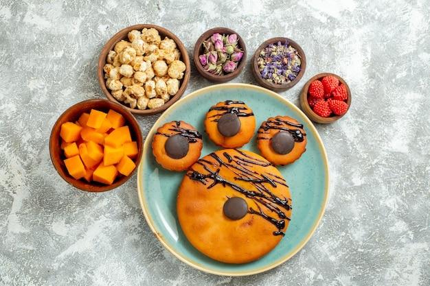 Bovenaanzicht lekkere cacaocakes met chocoladesuikerglazuur in de plaat op een witte oppervlaktekoekje, zoete cake, dessertkoekjestaart