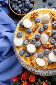 Bovenaanzicht lekkere cake met walnoten, verse bosbessen en koekjes op donkere ondergrond