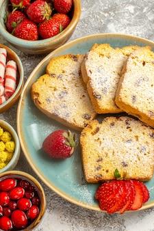Bovenaanzicht lekkere cake plakjes met aardbeien op licht