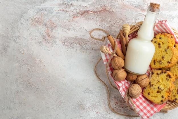 Bovenaanzicht lekkere cake plakjes met melk en walnoten op de witte achtergrond