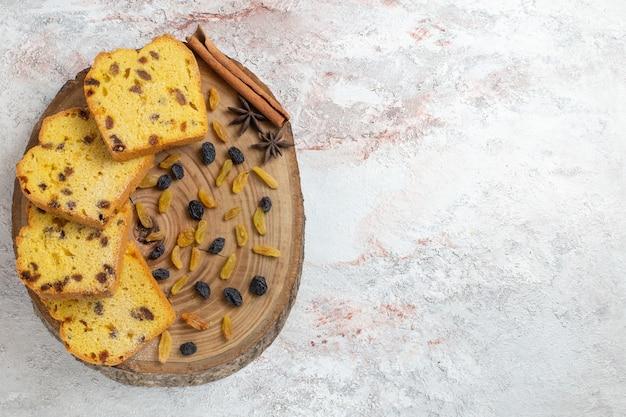 Bovenaanzicht lekkere cake plakjes met rozijnen op de witte achtergrond