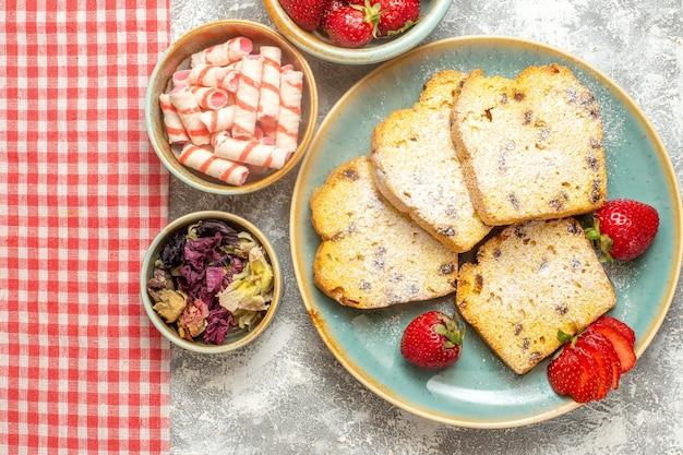 Bovenaanzicht lekkere cake plakjes met verse aardbeien op wit