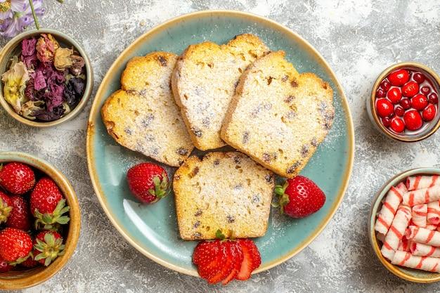 Bovenaanzicht lekkere cakeplakken met aardbeien en snoepjes op licht