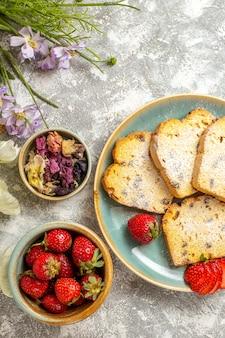 Bovenaanzicht lekkere cakeplakken met aardbeien en snoepjes op lichte vloer