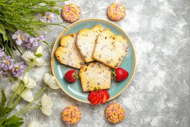Bovenaanzicht lekkere cakeplakken met aardbeien op lichte vloer