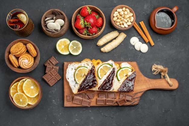 Bovenaanzicht lekkere cakeplakken met chocolade en fruit op donker bureau