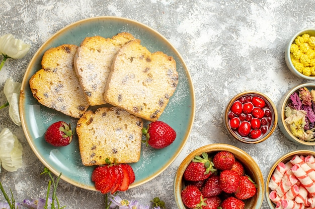 Bovenaanzicht lekkere cakeplakken met fruit en snoep op licht