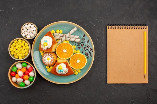 Bovenaanzicht lekkere cakeplakken met gesneden mandarijnen en snoepjes in het donker