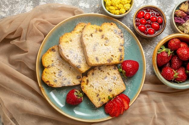 Bovenaanzicht lekkere cakeplakken met verse aardbeien op lichte vloer