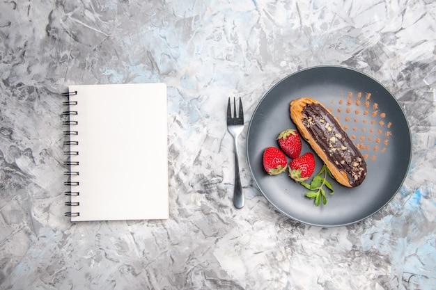 Bovenaanzicht lekkere choco eclairs met aardbeien op het lichte cake dessert snoep