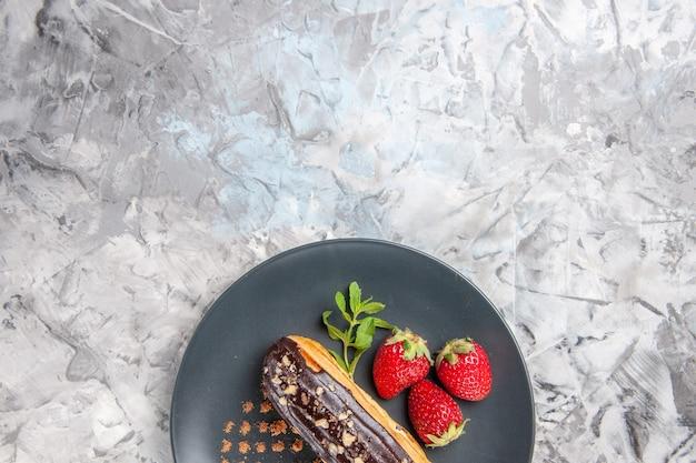 Bovenaanzicht lekkere choco-eclairs met aardbeien op licht dessertcakefruit