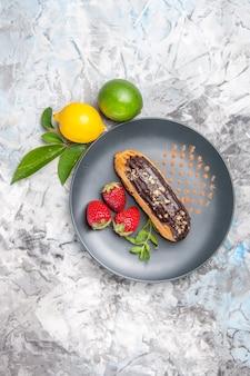 Bovenaanzicht lekkere choco-eclairs met aardbeien op lichte dessertkoekjes