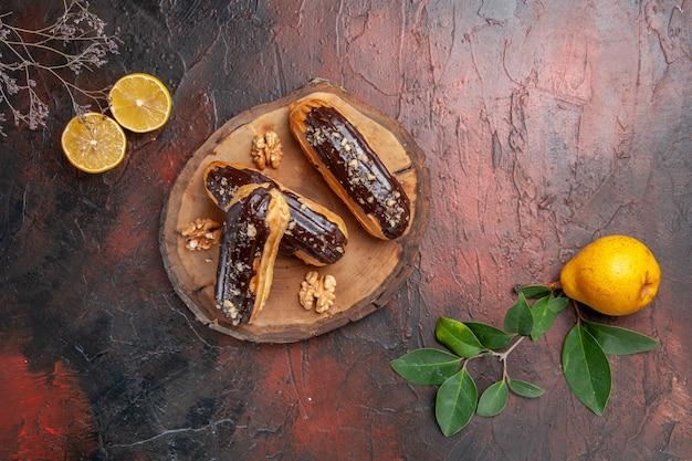 Bovenaanzicht lekkere choco eclairs met fruit op de donkere tafel taart dessert zoet