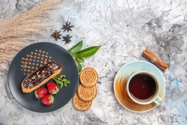 Bovenaanzicht lekkere choco-eclairs met koekjes op lichte koekjeskoekjesdessertcake
