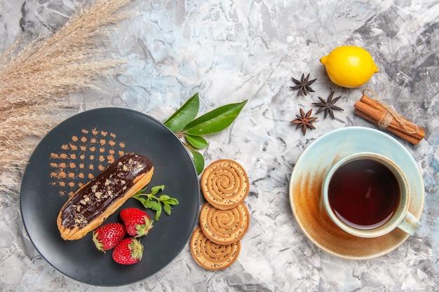 Bovenaanzicht lekkere choco-eclairs met kopje thee op een licht koekjesdessert