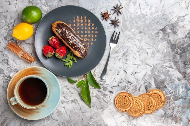 Bovenaanzicht lekkere choco-eclairs met kopje thee op een lichte biscuitdesserttaart
