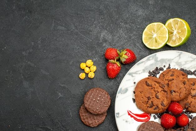Bovenaanzicht lekkere choco koekjes voor thee op de donkere achtergrond thee zoete koekjessuiker