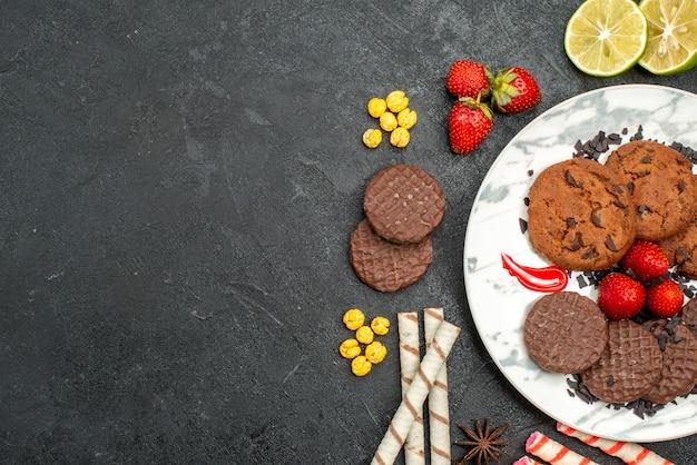 Bovenaanzicht lekkere choco koekjes voor thee op de donkere achtergrond zoete koekjes suiker thee