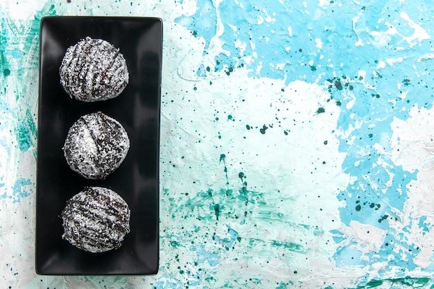 Bovenaanzicht lekkere chocolade ballen chocolade taarten met glazuur op het lichtblauwe oppervlak