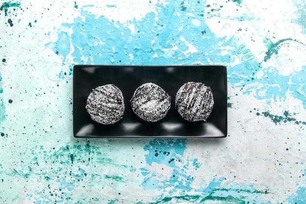 Bovenaanzicht lekkere chocolade ballen chocolade taarten met kers op het blauwe oppervlak