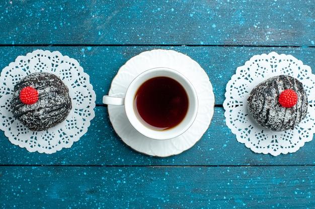 Bovenaanzicht lekkere chocolade ballen met kopje thee op blauw rustiek bureau thee cake koekje koekje zoet