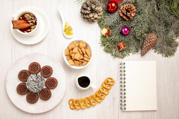 Bovenaanzicht lekkere chocoladekoekjes met kleine cacaocake en thee op het witte bureau