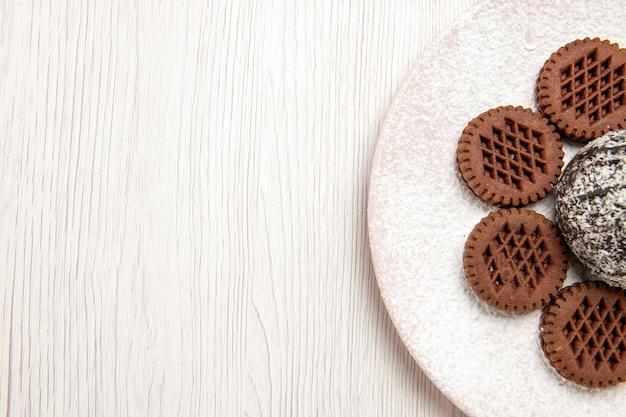 Bovenaanzicht lekkere chocoladekoekjes met kleine cacaocake op wit
