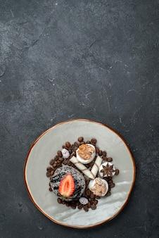 Bovenaanzicht lekkere chocoladetaart met chocoladeschilfers op grijs bureau