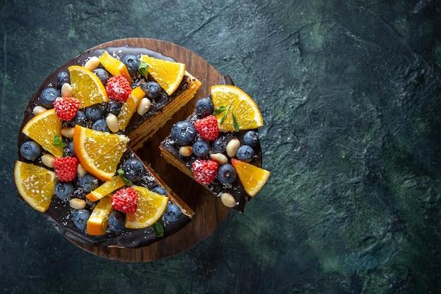 Bovenaanzicht lekkere chocoladetaart met fruit op donker