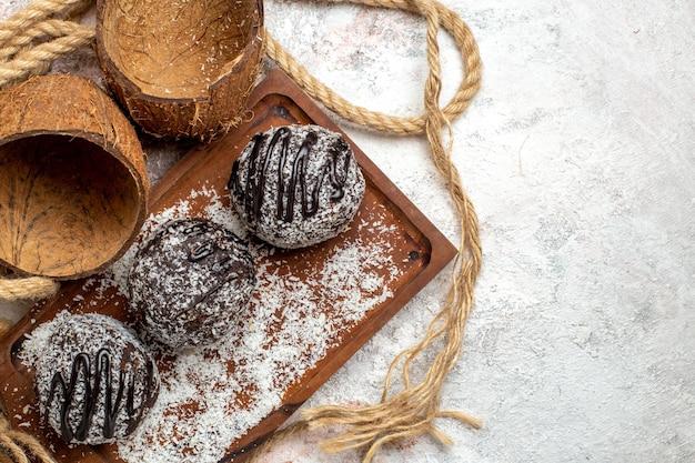 Bovenaanzicht lekkere chocoladetaarten met kokos op witte ondergrond