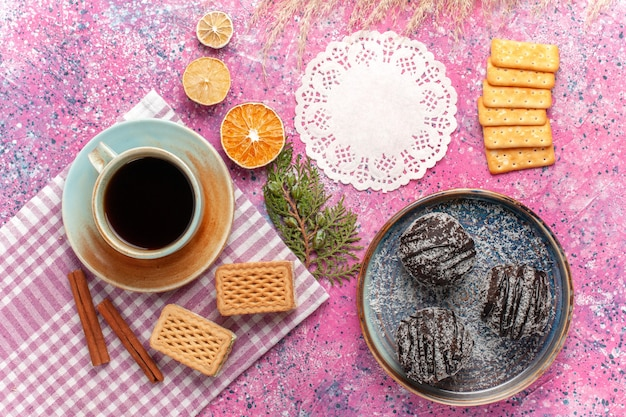 Bovenaanzicht lekkere chocoladetaarten met kopje thee en wafels op lichtroze