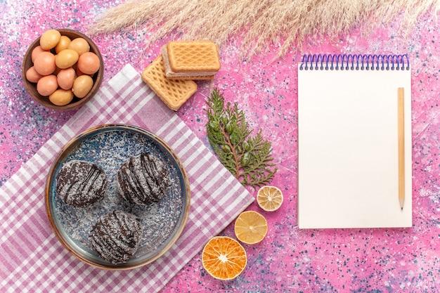 Bovenaanzicht lekkere chocoladetaarten met snoep en wafels op roze
