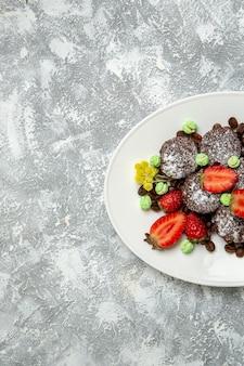 Bovenaanzicht lekkere chocoladetaarten met verse rode aardbeien en chocoladeschilfers op een wit bureau