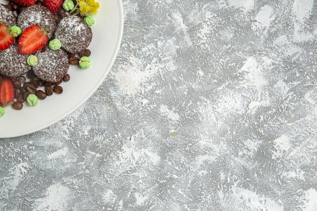 Bovenaanzicht lekkere chocoladetaarten met verse rode aardbeien en chocoladeschilfers op een witte ondergrond