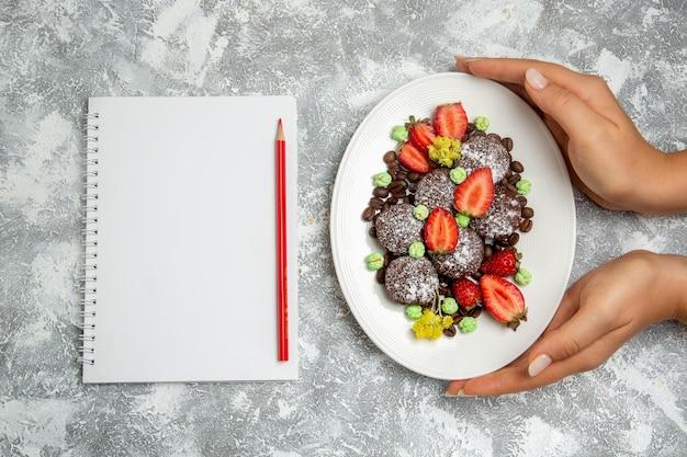 Bovenaanzicht lekkere chocoladetaarten met verse rode aardbeien en chocoladeschilfers op witte vloerkoek, chocolade, zoete cake, koekjes bakken