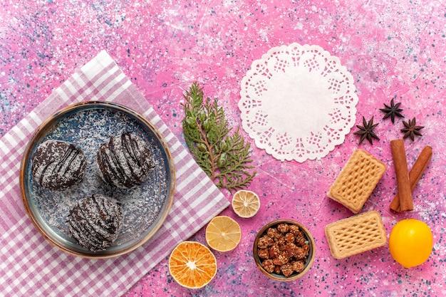 Bovenaanzicht lekkere chocoladetaarten met wafels en kaneel op roze