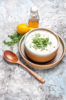 Bovenaanzicht lekkere dovga yoghurtsoep met greens op lichte witte soepschotel zuivel