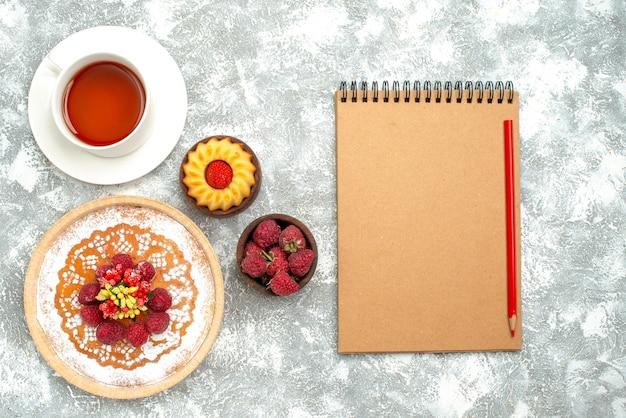 Bovenaanzicht lekkere frambozencake met kopje thee op witte oppervlakte taart biscuit thee zoete cake suiker