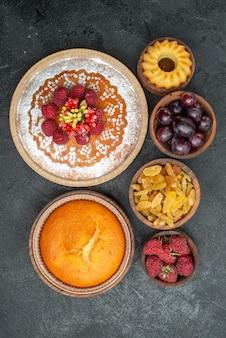 Bovenaanzicht lekkere frambozencake met rozijnen en fruit op het grijze oppervlak taart thee biscuit cake cookie sweet
