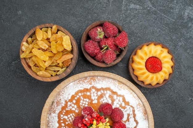 Bovenaanzicht lekkere frambozencake met rozijnen op grijs oppervlak sugar biscuit cake cookie tea zoete taart